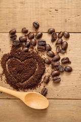 ground coffee in heart shape close to coffee beans on wooden table