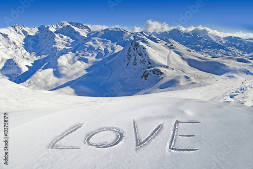 Love written in the snow, mountain landscape in the background