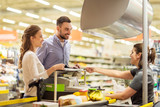couple buying food at grocery store cash register