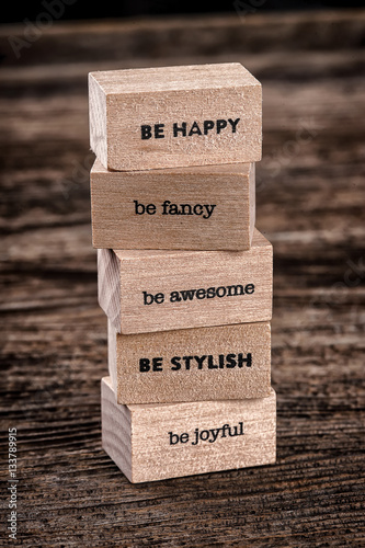 Poster Be happy and another text on a wooden cubes on a wooden background