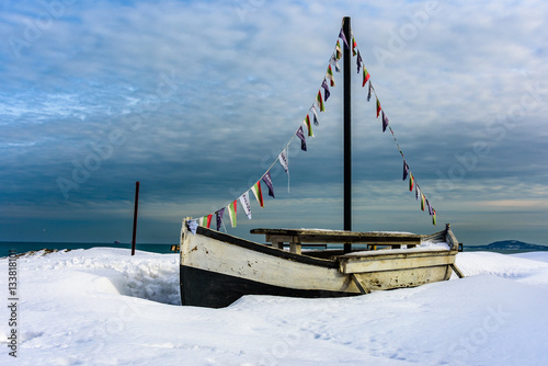 Poster, Tablou Child toy boat in snow at sea shore