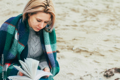 Poster A girl reads a book on the beach