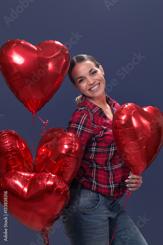 Poster Beautiful woman posing with red heart shaped balloon.