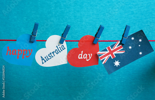 Poster Celebrate Australia Day holiday on January 26 with a Happy Australia Day message greeting written across white Australian maps (red heart) and flag hanging pegs on blue background