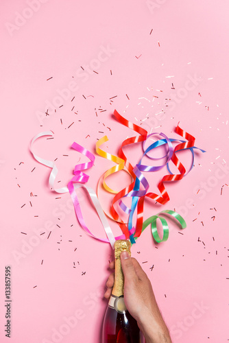 Flat lay of Celebration. Champagne bottle with colorful party st