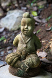 stone figurine on the ground among the leaves