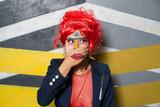 Retrato de chica joven con estética punk y post-punk (tribu urbana futurista) con peluca roja y con la cara pintada haciendo gestos provocativos