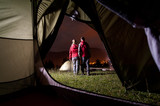 View from inside a tent on the couple tourist at night camping. They enjoy the view of beautiful mountains and night lights of the town
