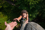 Young fearless woman climbing on large boulder, her male partner giving her a hand. Helping hand. View from the top
