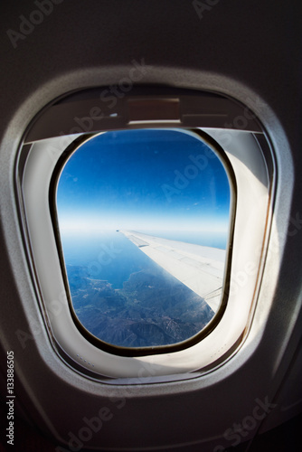 An airplane window with wing and aerial view of Corsica