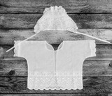 cap and shirt for a newborn on the old rustic wooden table close-up view from above. black and white photo