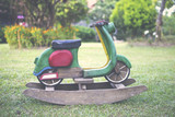 Wooden rocking scooter design in the garden, vintage tone style