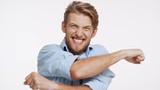 Caucasian young man with brown beard and blue eyes showing very actively yes on white background with great joy in slowmotion