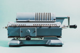 Old calculating machine on a green background. Accounting or bus