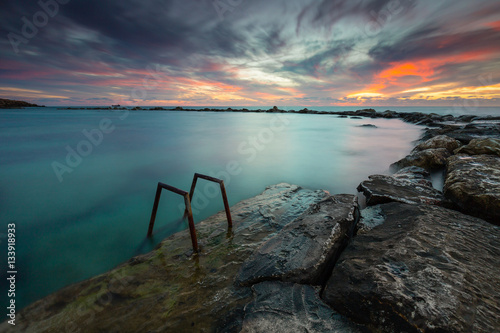 Long exposure seascape photograph of sunset from a rocky coast in Cyprus Poster