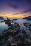 Long exposure seascape photograph of sunset from a rocky coast in Cyprus