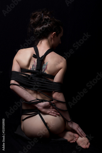 Nude woman in shirt with shibari in studio Poster