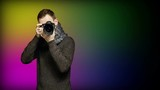Young man photographing you at professional digital SLR camera, looking at result and gesturing thumb up over colorful background