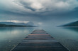 Dock overlooking a calm overcast lake.