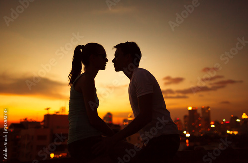 Young couple kissing at twilight.