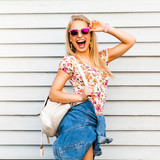 Portrait of a young blonde hipster. Girl with sunglasses dressed in shorts, T-shirt and posing in white wall - 133962110