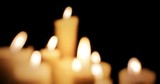 Blurred bokeh background of many burning candles glowing in darkness - 133967176
