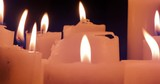 Close up view of many candles burning with warm fire in darkness 4K video background