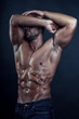 Handsome bodybuilder poses on dark background