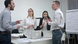 Cheerful office people applauding and shaking their hands after great work