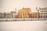 illuminated Brandenburg gate (Brandenburger Tor) and 18th of March Square in snow, Berlin, Germany, Europe, Vintage filtered style