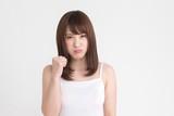 若い女性が、こぶしをふりあげて、怒りの表情をしています。