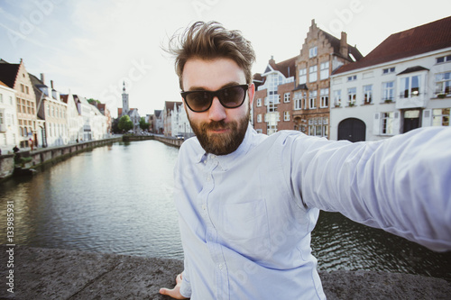 Poster Happy stylish man takes selfie photo in Amsterdam, Netherlands