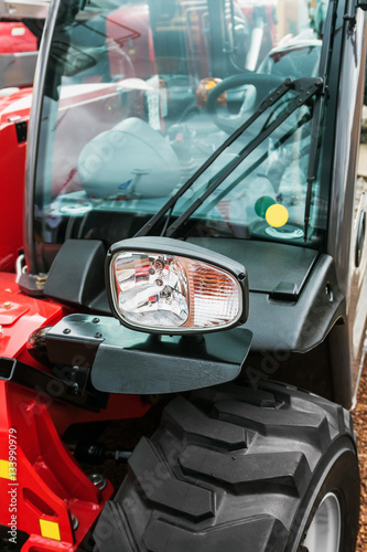 Poster parking lights on a red tractor. focus on the parking light