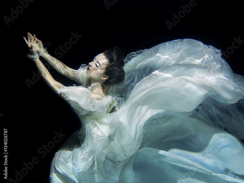 Plakat young girl in long white luxury dress underwater on the black background