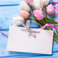 Empty tag, white and pink spring tulip, pink ribbon on blue w
