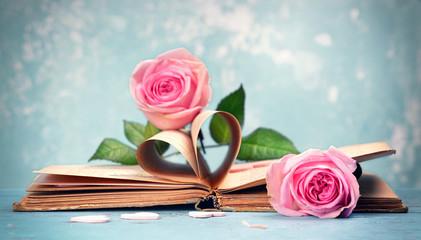 aufgeschlagenes Buch mit Seiten in Herzform und rosa Rosen
