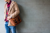 Mens casual outfits wear blue jeans with red plaid shirt, brown coat and leather bag standing over gray grunge background with space, lifestyle traveler, beauty and fashion concept