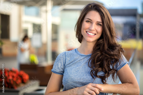 Big bright white smile headshot with a beautiful brunette woman sincere happy cheerful positive expression