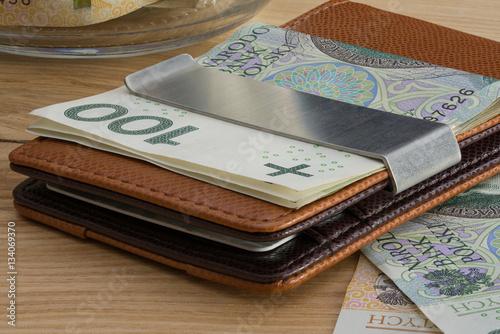 cienki portfel z polskimi banknotami i kartami płatniczymi na ceglanym tle