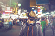 Young Asian traveling backpacker in Khaosan Road night market in evening in Bangkok, Thailand
