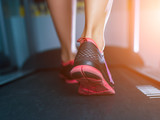 Fototapety Female muscular feet in sneakers running on the treadmill at the gym. Concept for fitness, exercising and healthy lifestyle.
