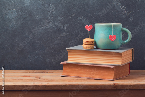 Poster Macarons Valentines day concept with tea cup and macarons on books over blackboard background