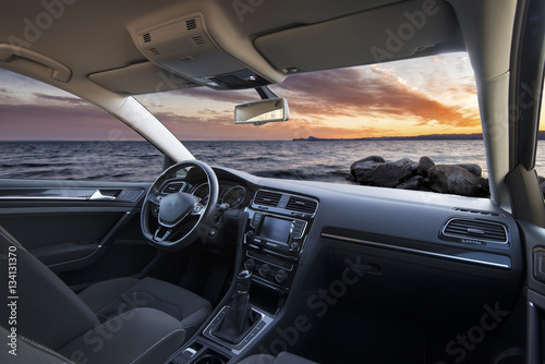 Poster beautiful sunset over the sea seen from the inside of a car