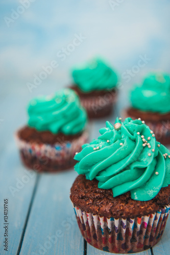 Poster Chocolate cupcakes with cream on blue background