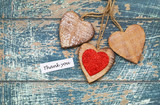 Thank you card with three wooden hearts on blue rustic wooden surface