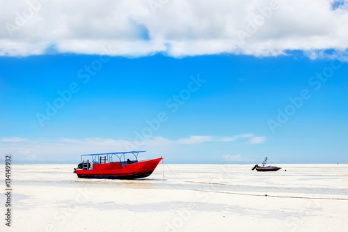 Foto op Plexiglas Zanzibar Red boat on the beach of Zanzibar on the blue sky background. Africa. Tanzania.