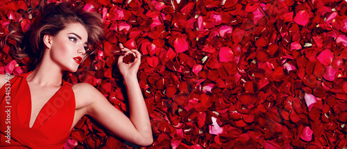 fototapeta na ścianę Valentine's Day. Loving girl. The girl in a red dress lying on the floor in the petals of red roses. Background of red rose petals. Red lipstick on the lips from the beautiful girl.