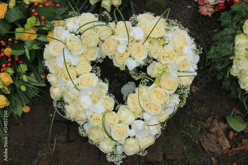 Heart shaped sympathy wreath near a tree