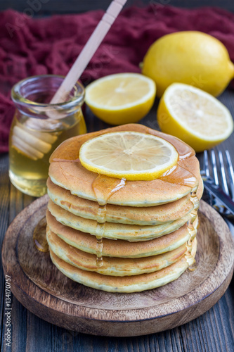 Poster Healthy homemade lemon and chia seed pancakes served with honey, vertical