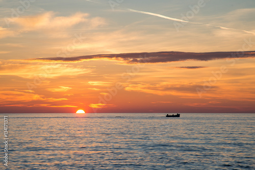 Poster Fishing boat on the background of incredible golden sunrise, clouds and rising sun